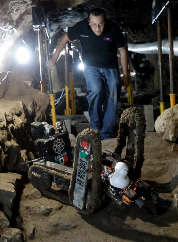 Image: A worker from the National Institute of Anthropology and History walks next to a robot used to explore ruins on the entrance of a tunnel in the archaeological area of the Quetzalcoatl Temple near the Pyramid of the Sun at the Teotihuacan  archaeolo